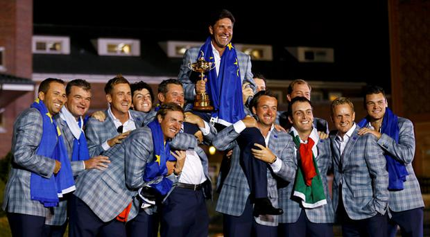 Europe captain Jose Maria Olazabal (C) of Spain is lifted up as he poses with the team