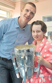 Kilkenny star Henry Shefflin hands over the Liam MacCarthy Cup to Kayla Dibble (14), from Roscommon Town, at Our Lady's Hospital, Crumlin, yesterday.