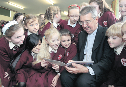 Archbishop of Dublin Dr Diarmuid Martin with some of the first holy communion class pupils at St Columba's National School in Glasnevin yesterday during the launch of the archdiocese's new policy document.