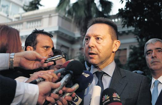 Greek Finance Minister Yannis Stournaras talks to reporters after a meeting with Greek Prime Minister Antonis Samaras and the troika in Athens yesterday. 'The troika wants clarifications,' Mr Stournaras told reporters