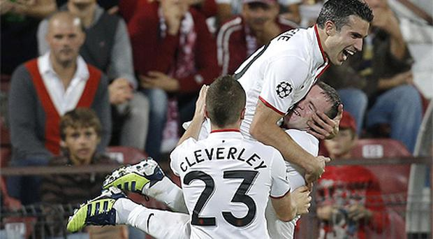 Robin van Persie celebrates with Wayne Rooney after scoring the winner against CFR Cluj