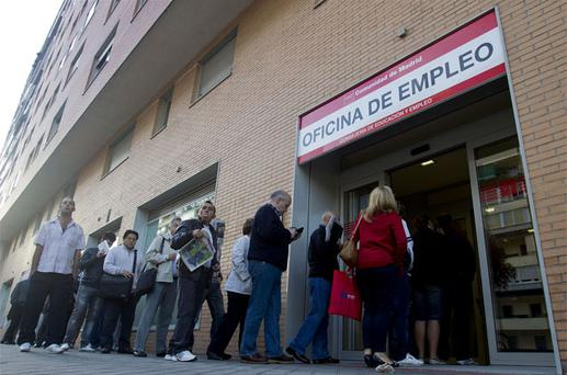 People queue to enter an unemployed registry office in Madrid