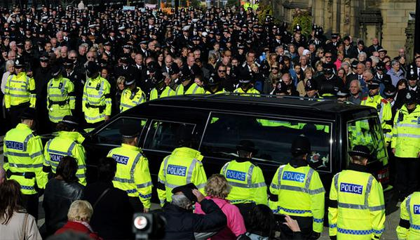 Police officers line the road as members of the public and colleagues watch as the coffin of Pc Nicola Hughes is driven from Manchester Cathedral