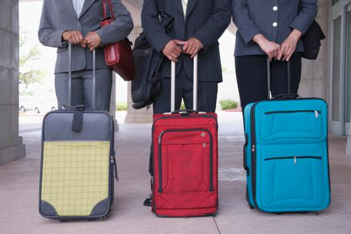 Mid section of three business people standing behind luggage