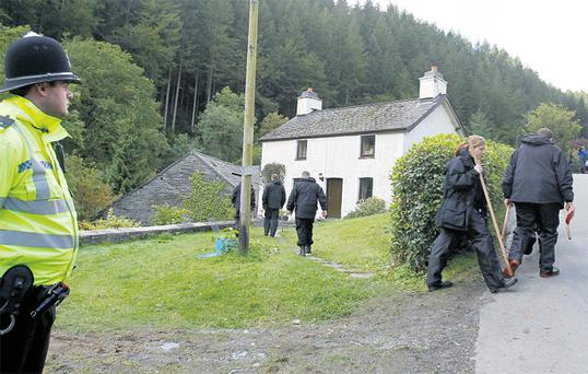 Police outside suspect Mark Bridger's rented cottage in Ceinws, Wales