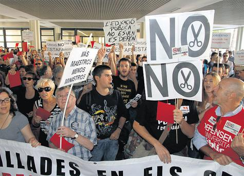 Spanish students boycotting the opening ceremony of the academic year hold signs during a protest against education cuts at the Polytechnic University of Valencia yesterday. Photo: Reuters