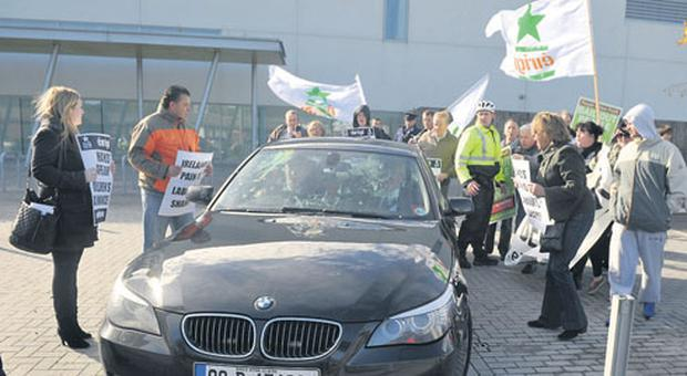 Protesters, carrying Eirigi and People Before Profit placards, block the car taking Eamon Gilmore and Frances Fitzgerald to a UNICEF launch in Ballyfermot