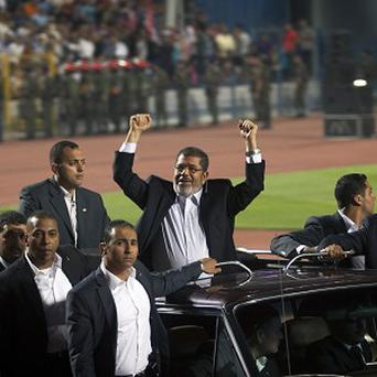 Egyptian president Mohammed Morsi greets the crowds in Cairo (AP)
