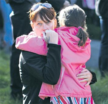 A mother holds her little one as hundreds pay their respects at an emotional service for missing April Jones