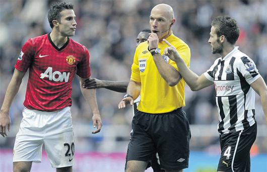 Referee Howard Webb intervenes as Newcastle's Yohan Cabaye (R) and Manchester United's Robin van Persie exchange words