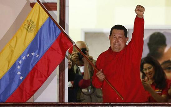 Venezuelan President Hugo Chavez waves the national flag while celebrating from a balcony at Miraflores Palace in Caracas. Photo: Reuters