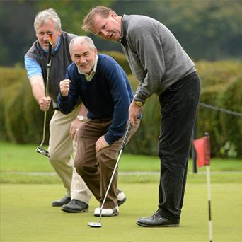 Comedian Barry Murphy and football manager Mickey Harte watch as former soccer star Ronnie Whelan makes a putt at the Irish Motor Neurone Disease Association Golf Classic at Carton House, Co Kildare