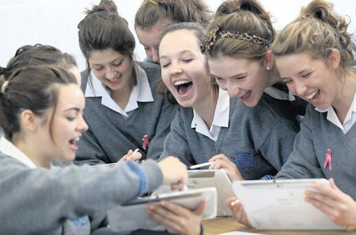 Aisling Costello (centre) with her fellow Loreto Secondary School students learning to use their tablets