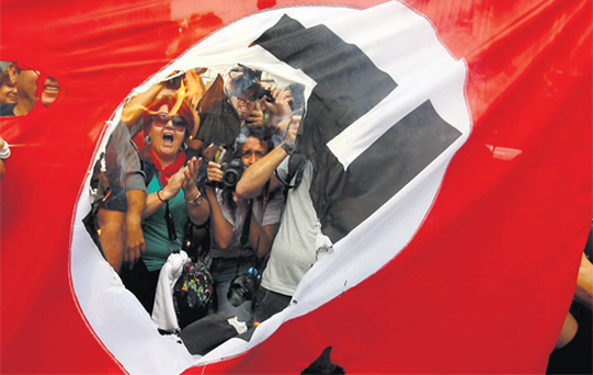 Demonstrators burn a flag emblazoned with a swastika during a demonstration against the visit of German Chancellor Angela Merkel in central Athens.