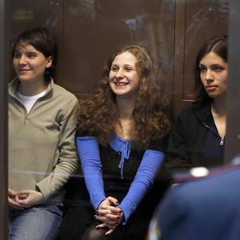 Pussy Riot members Maria Alekhina, Yekaterina Samutsevich and Nadezhda Tolokonnikova sit in a glass cage at a courtroom in Moscow (AP)