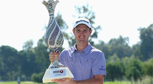 Justin Rose of England poses with the trophy after beating Lee Westwood
