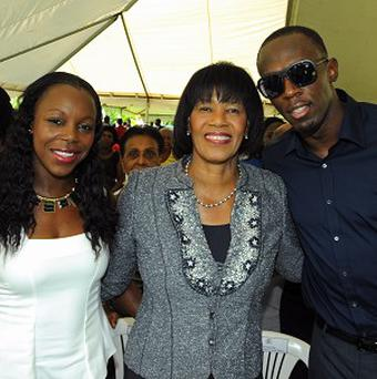 Sprint star Usain Bolt and fellow athlete Veronica Campbell with Jamaica's Prime Minister Portia Simpson Miller, centre (AP)