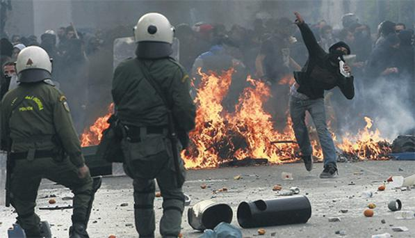 A protester throws stones at police in Athens, Greece