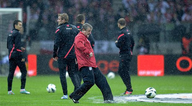 England manager Roy Hodgson tests the condition of the pitch in the pouring rain