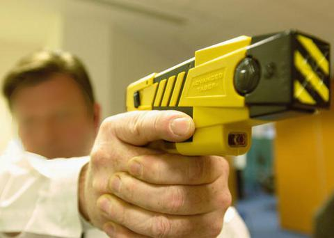 A police officer demonstrates the use of a taser. Photo: Getty Images