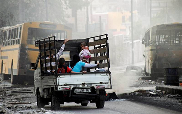 A family on a pick-up truck flees violence in the city of Aleppo.