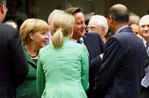 Germany's Chancellor Angela Merkel (L) and Britain's Prime Minister David Cameron (C) chat with other leaders at a European Union leaders summit in Brussels