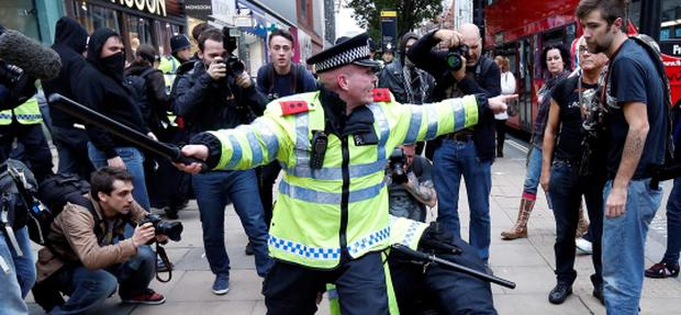 Police officer detain a demonstrator during a protest march organised by the Trades Union Congress (TUC), in Oxford Street, in central London October 20, 2012. Thousands of British protesters marched through central London on Saturday against public spending cuts and tax rises enacted by a government fighting accusations it is run by an upper-class elite that ignores the plight of recession-hit voters. REUTERS/Suzanne Plunkett (BRITAIN - Tags: BUSINESS POLITICS EMPLOYMENT)