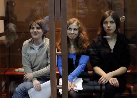 Members of the female punk band 'Pussy Riot' (L-R) Yekaterina Samutsevich, Maria Alyokhina and Nadezhda Tolokonnikova sit in a glass-walled cage before a court hearing in Moscow.