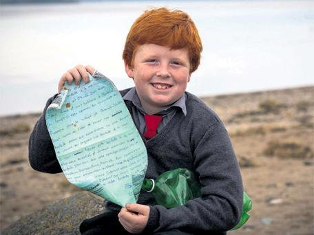Oisin Millea with the message in a bottle which he found on the beach at Passage East in Co Waterford, eight years after it was written by two girls from Quebec