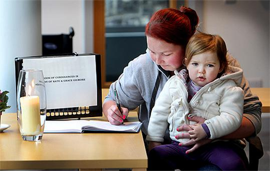 Amy Barry signs the book of condolences as she holds her daughter Aoife