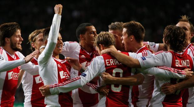 AMSTERDAM, NETHERLANDS - OCTOBER 24: Christian Eriksen (#8) of Ajax celebrates with team mates after he shoots and scores his teams third goal of the game during the Group D UEFA Champions League match between AFC Ajax and Manchester City FC at Amsterdam ArenA on October 24, 2012 in Amsterdam, Netherlands. (Photo by Dean Mouhtaropoulos/Getty Images)