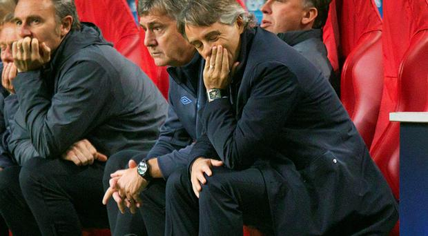 Manager Roberto Mancini and a despondent Manchester City bench look on towards the end of their Champions League defeat at the hands of Ajax