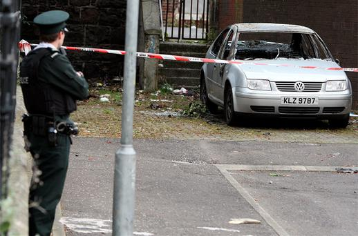 Police stand by a burnt out car in west Belfast, which is linked to a fatal shooting in Newtownabbey, Co Antrim, last night. Photo: PA