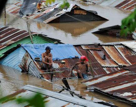 People sit on the rooftop of houses submerged in floodwaters in the neighbourhood of Barquita, after days of heavy rain in Santo Domingo, October 26, 2012. Hurricane Sandy, a late-season Atlantic storm unlike anything seen in more than two decades, slogged slowly toward the U.S. East Coast on Friday after killing at least 41 people as it cut across the Caribbean. REUTERS/Ricardo Rojas (DOMINICAN REPUBLIC - Tags: DISASTER ENVIRONMENT)