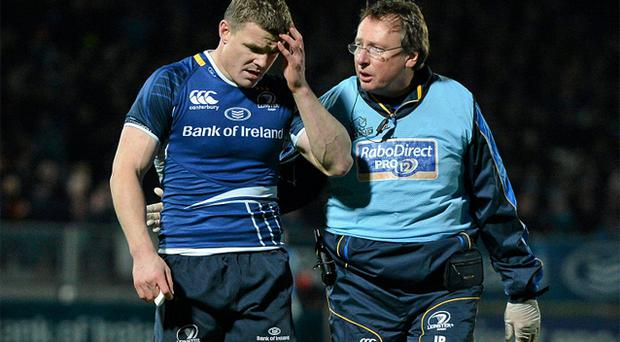 Leinster's Brian O'Driscoll leaves the pitch with an injury accompanied by team doctor John Ryan. Photo: Sportsfile