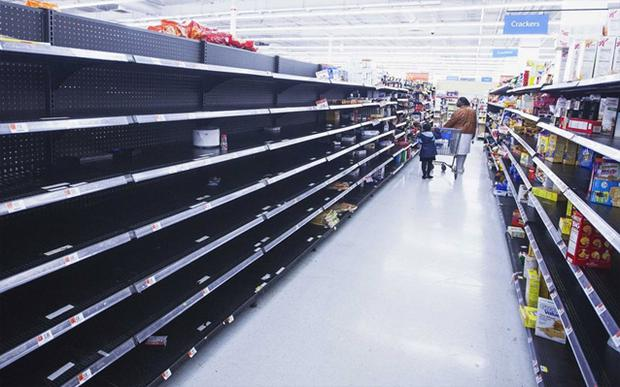 A woman and child walk through an aisle, emptied in preparation for Hurricane Sandy, in a Wal-Mart store in Riverhead, New York. Photo: Reuters