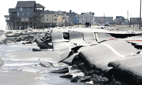 The North Carolina 12 road is buckled from pounding surf in Rodanthe