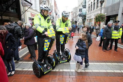 Specially-trained gardai Dabhach Dineen (left) and David Campbell meet Darragh and Katie Burke from Galway on Grafton Street, as they begin patrolling the city centre on two new segways donated by Dublin City Business Association today. Photo: PA