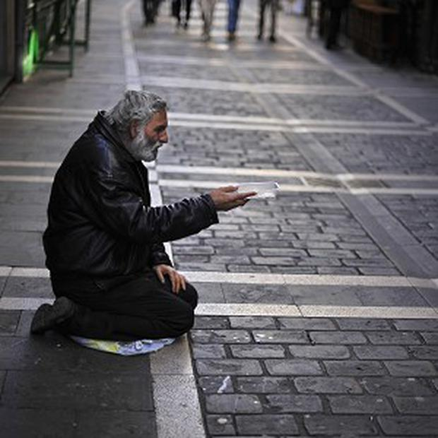 A jobless man begs in Pamplona, Spain (AP)