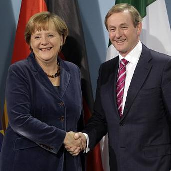 German chancellor Angela Merkel and Enda Kenny shake hands. (AP Photo/Michael Sohn)