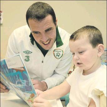 Republic of Ireland's John O'Shea, helps Luke Concannon, age 7, from Lucan, Co. Dublin, with his maths, on a visit to Temple Street Children's Hospital ahead of their FIFA World Cup Qualifier match against Germany on Friday