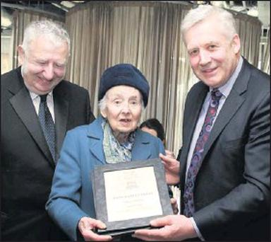 Minister Fergus O'Dowd presents 93-year-old Anne O'Brien with her Google Silver Surfer Award at Google headquarters, while her son Sean looks on. Anne has written a thesis on the history of the McClintock Estate in Drumcar.