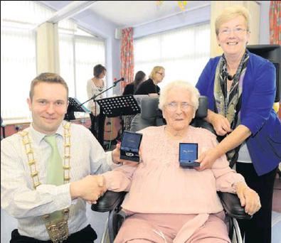 Molly Murray receives her 102nd medal from Mayor Cian O'Callaghan on behalf of President Michael D Higgins along with her 101st medal she received from former President Mary McAleese, held by daughter Eleanor.