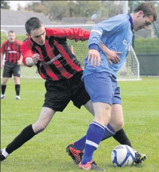 Kyle Dempsey of North End United tries to find a way past Riley Ronan-John (Bridge Rovers) in their F.A.I. Junior Cup first round clash on Sunday last which the town team won 5-0.