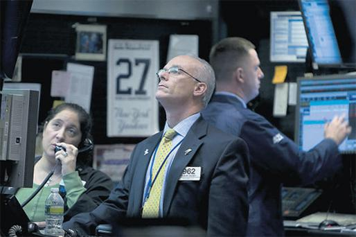 Traders, including Kevin Cassidy, centre, working on the floor of the New York Stock Exchange yesterday
