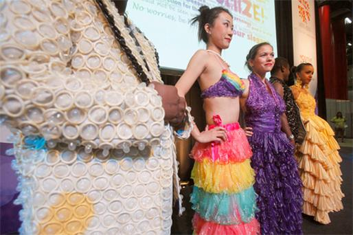 ls wear clothes made out of condoms at an exhibition during the 18th World Aids Conference in Vienna yesterday