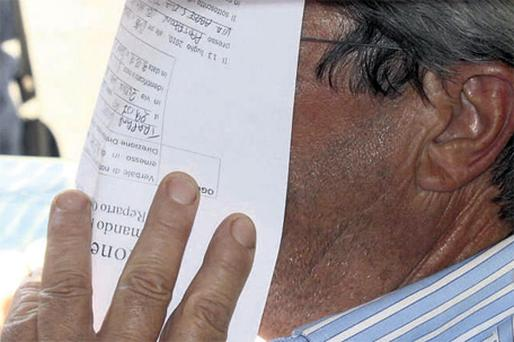 An unidentified man covers his face with an arrest warrant outside the police headquarters in Reggio Calabria, southern Italy, following one of the biggest operations ever against the powerful 'ndrangheta crime organisation