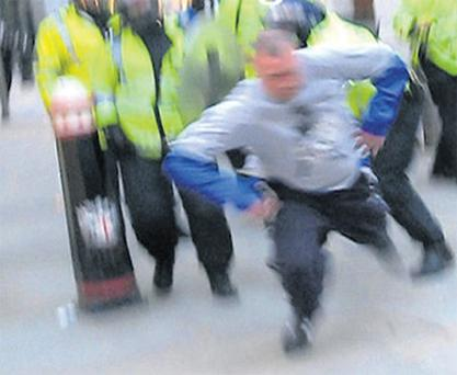 Blurred footage of the moment when Ian Tomlinson was pushed to the ground by a police officer