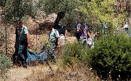 Spanish civil guards carrying the body of the as-yet-unnamed boy, whose body was found near a reservoir in Espiel