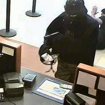 A person wearing a Darth Vader mask and cape is captured on surveillance camera robbing a Chase bank in Setauket, New York (AP)